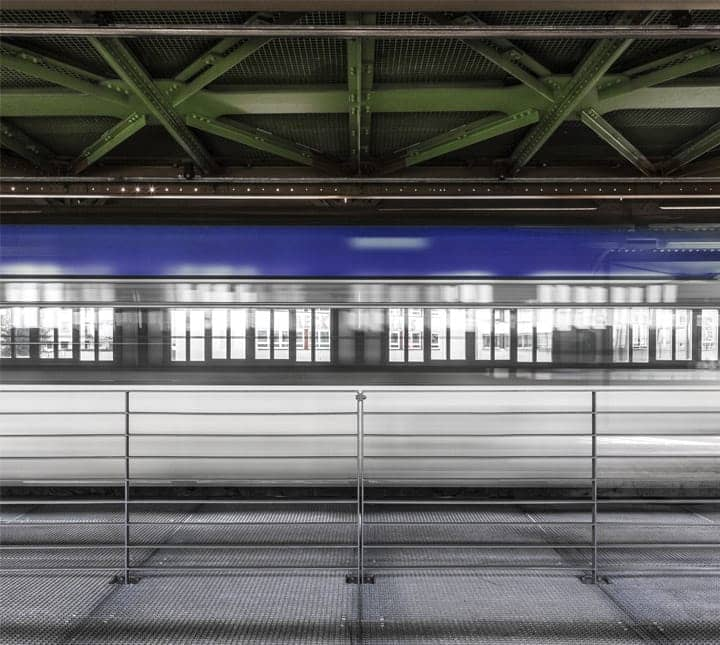 Thumbnail image of a blue and white train in motion inside a train station