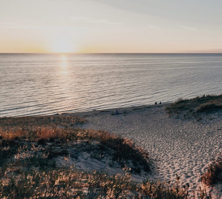 Thumbnail image of a sunset over the ocean with sand dunes and people on the beach