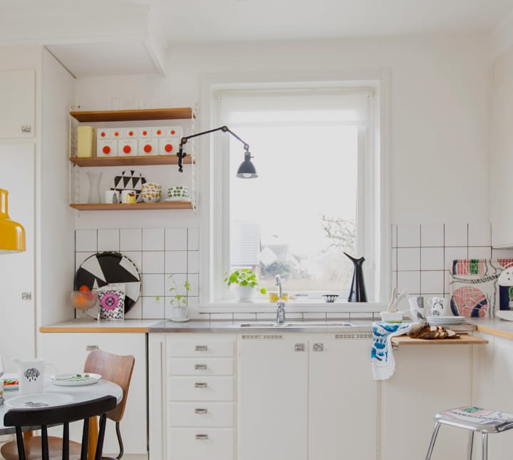 Thumbnail image of a small retro white kitchen with a dining table and window