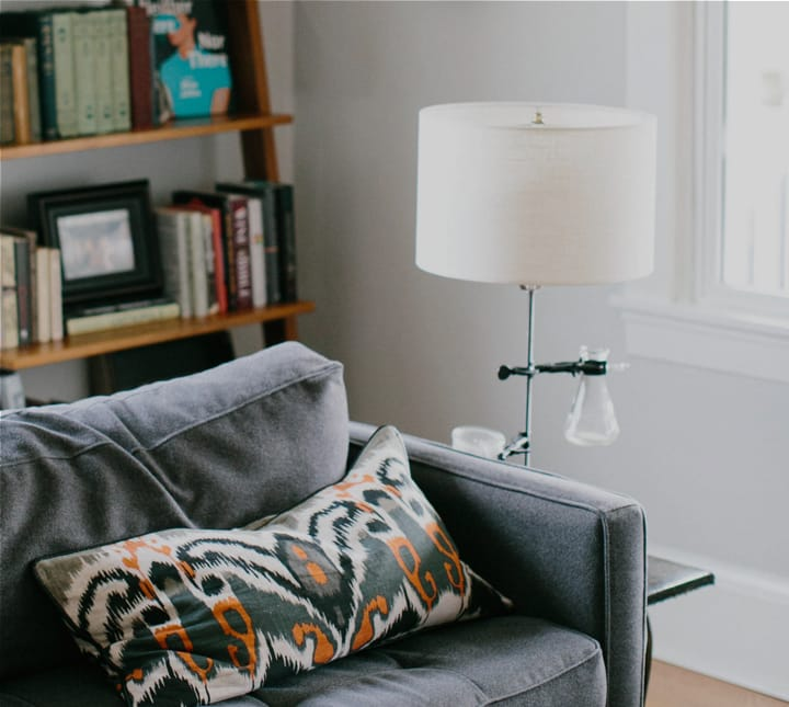 Thumbnail image of a grey sofa in a living room with a lamp and wooden bookshelves
